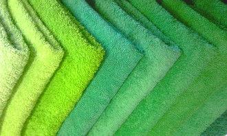 Стопка зеленых махровых полотенец различного оттенка